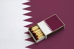Le drapeau du Qatar est montré dans une boîte d'allumettes ouverte, qui est remplie de matchs et se trouve sur un grand drapeau images libres de droits