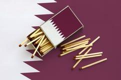 Le drapeau du Qatar est montré sur une boîte d'allumettes ouverte, de laquelle plusieurs matchs tombent et des mensonges sur un g photographie stock libre de droits