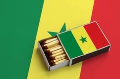 Le drapeau du Sénégal est montré dans une boîte d'allumettes ouverte, qui est remplie de matchs et se trouve sur un grand drapeau image stock