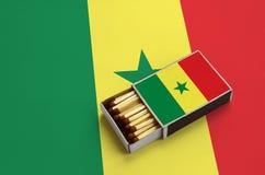 Le drapeau du Sénégal est montré dans une boîte d'allumettes ouverte, qui est remplie de matchs et se trouve sur un grand drapeau images libres de droits