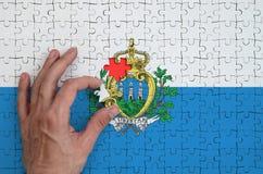 Le drapeau du Saint-Marin est dépeint sur un puzzle, que la main du ` s d'homme accomplit pour plier images libres de droits
