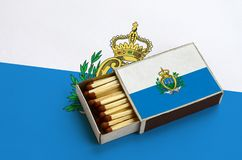 Le drapeau du Saint-Marin est montré dans une boîte d'allumettes ouverte, qui est remplie de matchs et se trouve sur un grand dra images libres de droits