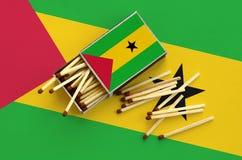 Le drapeau du Sao-Tomé-et-Principe est montré sur une boîte d'allumettes ouverte, de laquelle plusieurs matchs tombent et des men photo stock