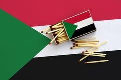 Le drapeau du Soudan est montré sur une boîte d'allumettes ouverte, de laquelle plusieurs matchs tombent et des mensonges sur un  image stock