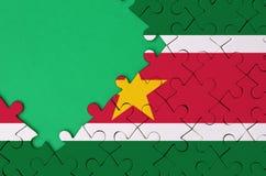 Le drapeau du Surinam est dépeint sur un puzzle denteux réalisé avec l'espace vert gratuit de copie du côté gauche photo libre de droits