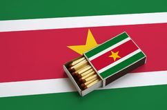 Le drapeau du Surinam est montré dans une boîte d'allumettes ouverte, qui est remplie de matchs et se trouve sur un grand drapeau images libres de droits