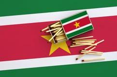 Le drapeau du Surinam est montré sur une boîte d'allumettes ouverte, de laquelle plusieurs matchs tombent et des mensonges sur un images stock