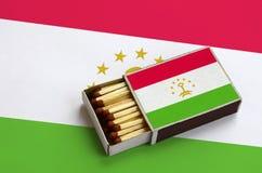 Le drapeau du Tadjikistan est montré dans une boîte d'allumettes ouverte, qui est remplie de matchs et se trouve sur un grand dra photos libres de droits