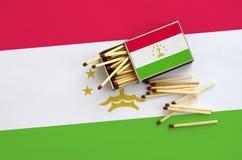 Le drapeau du Tadjikistan est montré sur une boîte d'allumettes ouverte, de laquelle plusieurs matchs tombent et des mensonges su photographie stock libre de droits