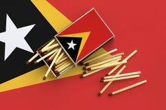 Le drapeau du Timor oriental est montré sur une boîte d'allumettes ouverte, de laquelle plusieurs matchs tombent et des mensonges photographie stock