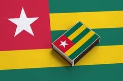 Le drapeau du Togo est décrit sur une boîte d'allumettes qui se trouve sur un grand drapeau photographie stock