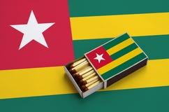 Le drapeau du Togo est montré dans une boîte d'allumettes ouverte, qui est remplie de matchs et se trouve sur un grand drapeau image libre de droits