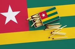 Le drapeau du Togo est montré sur une boîte d'allumettes ouverte, de laquelle plusieurs matchs tombent et des mensonges sur un gr images stock