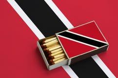 Le drapeau du Trinidad-et-Tobago est montré dans une boîte d'allumettes ouverte, qui est remplie de matchs et se trouve sur un gr photographie stock