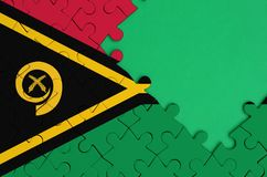 Le drapeau du Vanuatu est dépeint sur un puzzle denteux réalisé avec l'espace vert gratuit de copie du côté droit photos stock