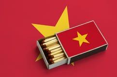 Le drapeau du Vietnam est montré dans une boîte d'allumettes ouverte, qui est remplie de matchs et se trouve sur un grand drapeau image stock