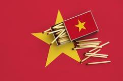 Le drapeau du Vietnam est montré sur une boîte d'allumettes ouverte, de laquelle plusieurs matchs tombent et des mensonges sur un photo libre de droits