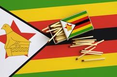 Le drapeau du Zimbabwe est montré sur une boîte d'allumettes ouverte, de laquelle plusieurs matchs tombent et des mensonges sur u photo libre de droits