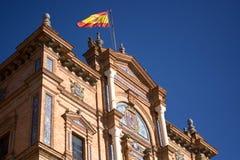 Le drapeau espagnol ondulant dans le vent en Plaza de Espana en Séville Images libres de droits