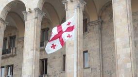 Le drapeau géorgien flotte dans le vent en haut du bâtiment de gouvernement clips vidéos