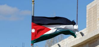 Le drapeau jordanien ondulant dans le vent devant le centre de touristes et le visiteur centrent près du château de croisé dans K photos libres de droits