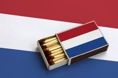 Le drapeau néerlandais est montré dans une boîte d'allumettes ouverte, qui est remplie de matchs et se trouve sur un grand drapea photo stock