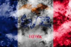 Le drapeau national de l'état d'USA Iowa dedans contre une fumée grise le jour de l'indépendance dans différentes couleurs de rou illustration stock