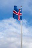 Le drapeau national de l'Islande ondulant en ciel bleu Image stock
