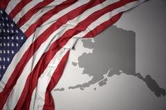 Le drapeau national de ondulation des Etats-Unis d'Amérique sur l'Alaska gris énoncent le fond de carte Image libre de droits