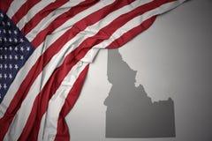 Le drapeau national de ondulation des Etats-Unis d'Amérique sur l'Idaho gris énoncent le fond de carte Photographie stock libre de droits