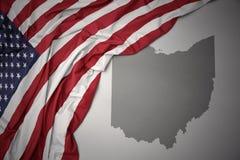 Le drapeau national de ondulation des Etats-Unis d'Amérique sur l'Ohio gris énoncent le fond de carte Photographie stock