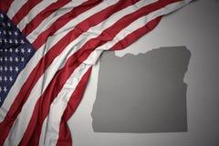 Le drapeau national de ondulation des Etats-Unis d'Amérique sur l'Orégon gris énoncent le fond de carte Photographie stock