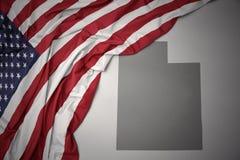 Le drapeau national de ondulation des Etats-Unis d'Amérique sur l'Utah gris énoncent le fond de carte Images stock
