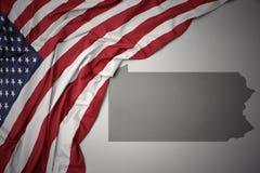 Le drapeau national de ondulation des Etats-Unis d'Amérique sur la Pennsylvanie grise énoncent le fond de carte Photographie stock libre de droits