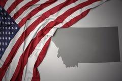 Le drapeau national de ondulation des Etats-Unis d'Amérique sur le Montana gris énoncent le fond de carte Image stock