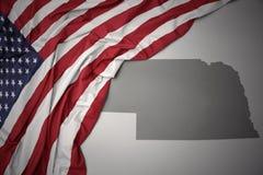 Le drapeau national de ondulation des Etats-Unis d'Amérique sur le Nébraska gris énoncent le fond de carte Image libre de droits