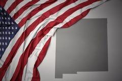Le drapeau national de ondulation des Etats-Unis d'Amérique sur le Nouveau Mexique gris énoncent le fond de carte Photo libre de droits