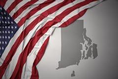 Le drapeau national de ondulation des Etats-Unis d'Amérique sur le Rhode Island gris énoncent le fond de carte Photographie stock libre de droits