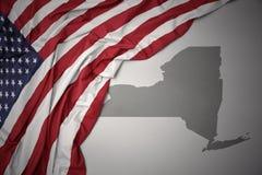 Le drapeau national de ondulation des Etats-Unis d'Amérique sur un état de New-York gris tracent le fond Image stock