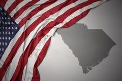 Le drapeau national de ondulation des Etats-Unis d'Amérique sur une Caroline du Sud grise énoncent le fond de carte Photographie stock