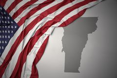 Le drapeau national de ondulation des Etats-Unis d'Amérique sur le Vermont gris énoncent le fond de carte Images stock