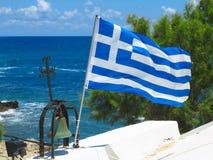 Le drapeau national grec près de la croix de la petite église contre le bleu Image libre de droits