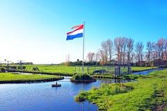 Le drapeau national néerlandais dans un paysage néerlandais Photographie stock