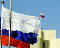 Le drapeau russe sur le bâtiment sur le fond du ciel bleu images stock