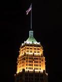 Le drapeau vole au-dessus du bâtiment de la vie de tour la nuit Images stock
