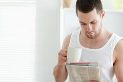 Le dricka kaffe för manen fördriver läsning nyheterna Arkivbilder