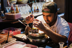 LE DUBAÏ, EMIRATS ARABES UNIS - 7 DÉCEMBRE 2016 : L'artisan fait des souvenirs dans une bouteille utilisant le sable coloré Photos libres de droits