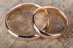 Le due fedi nuziali dell'oro su fondo di legno Fotografia Stock Libera da Diritti