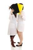 Le due giovani infermiere con un dispositivo di piegatura isolato Immagini Stock Libere da Diritti