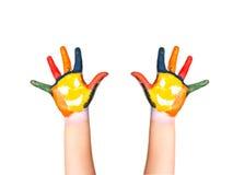 Le due mani variopinte con il sorriso dipinto con differenti colori del bambino come logo. Fotografie Stock